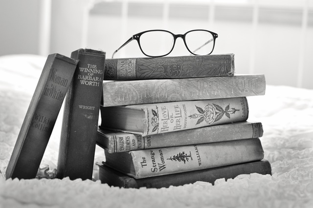 A pile of books & a pair of spectacles on top