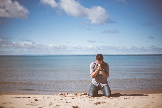 Man praying on beach